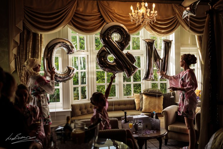 the bride and her bridesmaids arranging blown up balloons