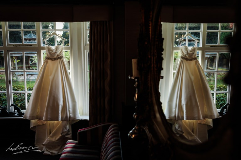 the brides dress hung in the window